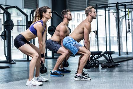 en cuclillas: Vista lateral de tres atletas musculosos en cuclillas con pesas