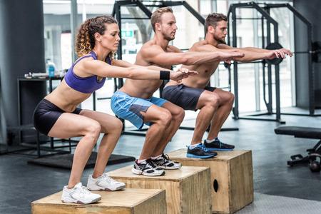 muscular: Tres atletas musculosos haciendo sentadillas saltando en una caja de madera