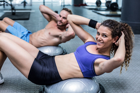 sit up: Portrait of a muscular couple doing bosu ball exercises