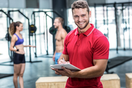 clipboard: Portrait of a muscular trainer writing on clipboard