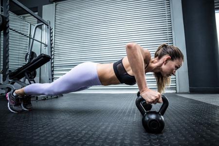 resistencia: Vista lateral de una mujer haciendo flexiones de brazos con pesas
