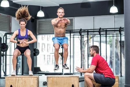 jumping: Entrenador supervisar atletas musculosos haciendo sentadillas saltando Foto de archivo