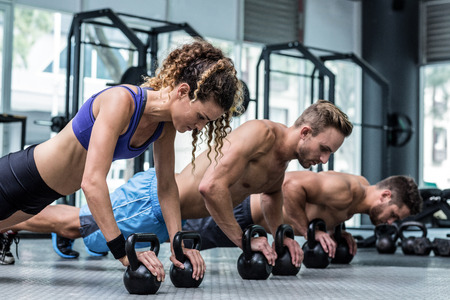 planking: Three muscular athletes on a plank position with kettlebells