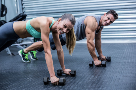 planking: Portrait of muscular couple doing plank exercise together