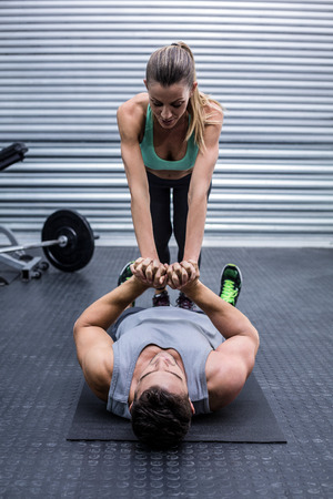 crossfit: Muscular couple doing core exercises at the crossfit gym Stock Photo