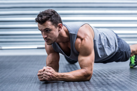 plank position: A muscular man on plank position at the crossfit gym
