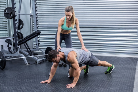 plank position: Female coach supervising a muscular man on a plank position
