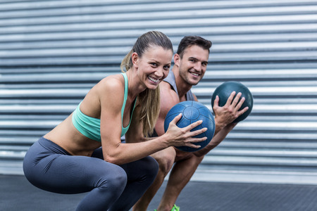exercise room: Portrait of a squatting muscular couple doing ball exercise Stock Photo
