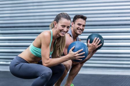 en cuclillas: Retrato de un ejercicio de pelota pareja musculoso cuclillas haciendo Foto de archivo