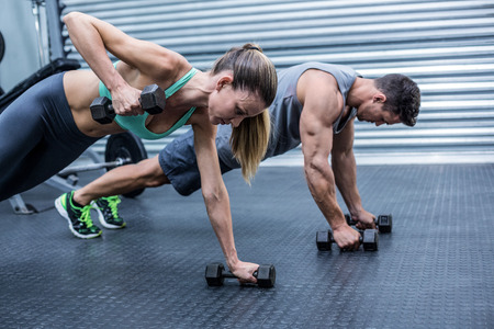 weight room: Muscular couple doing plank exercise while lifting weights