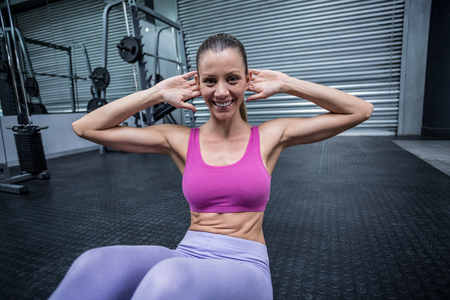 crunch: Portrait of a smiling woman doing abdominal crunch