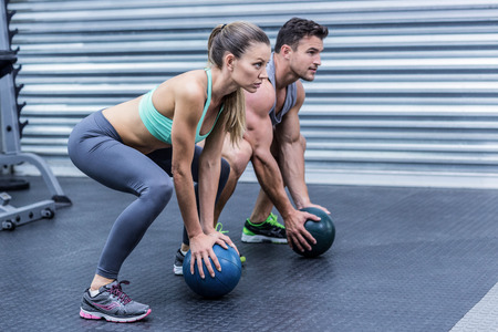 Squatting muscular couple doing ball exercise Stock Photo