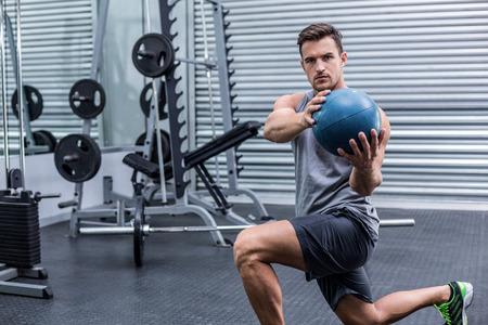 medecine: Portrait of a muscular man doing medecine ball exercises Stock Photo