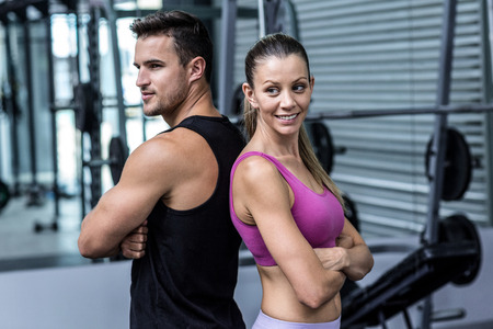 giving back: Muscular couple giving back to back with arm crossed Stock Photo