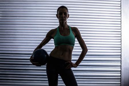 Muskulöse Frau mit einem Medizinball in einem dunklen Hintergrund