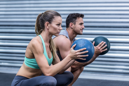 crossfit: Squatting muscular couple doing ball exercise Stock Photo