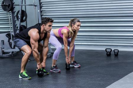 en cuclillas: Eyacular musculares pesas levantamiento pareja en el gimnasio crossfit