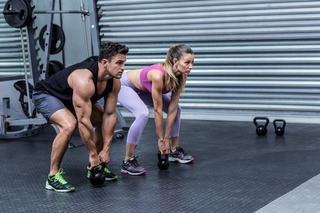 Squatting muscular couple lifting kettlebells at the crossfit gym