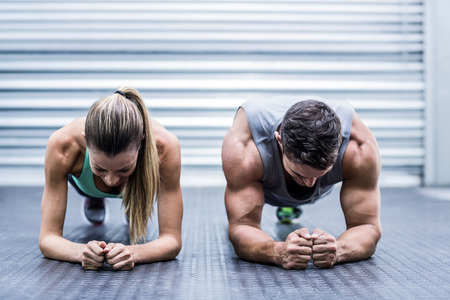 gym: Front view of a muscular couple doing planking exercises Stock Photo