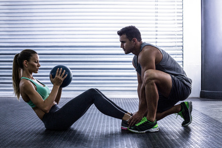 gym room: Side view of a muscular couple doing abdominal ball exercise