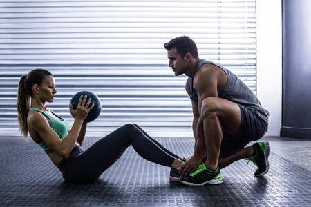 atleta: Vista lateral de una pareja muscular que hace ejercicio bola abdominal