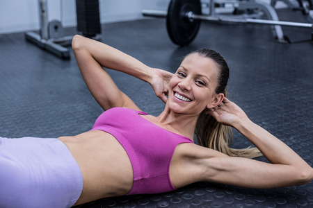 sit up: Portrait of a muscular woman doing abdominal crunch