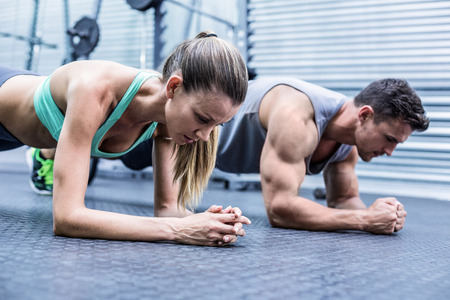 gym room: Side view of a muscular couple doing planking exercises