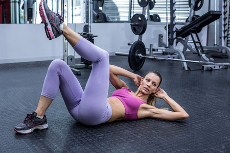crunch: Muscular woman doing abdominal crunch at the crossfit gym Stock Photo