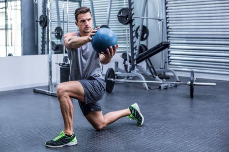 medecine: Muscular man doing medecine ball exercises at the crossfit gym Stock Photo