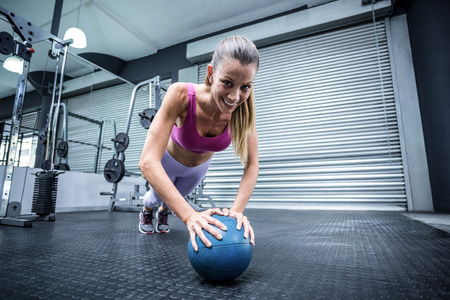 balance ball: Muscular woman on a plank position with a balance ball Stock Photo