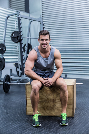 cuerpo hombre: Retrato de un hombre musculoso sentado en una caja de madera