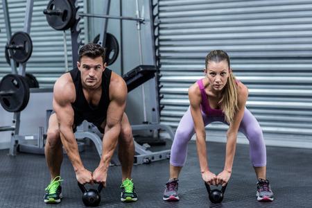 weight room: Portrait of a muscular couple lifting kettlebells at the health club