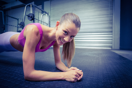 plank position: Portrait of a muscular woman on a plank position Stock Photo