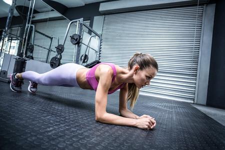 fuerza: Vista lateral de una mujer muscular en una posición de tabla