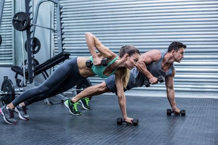 levantar peso: Pareja muscular que hace ejercicio del tablón mientras levanta pesas Foto de archivo