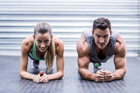 Portrait of a muscular couple doing planking exercises