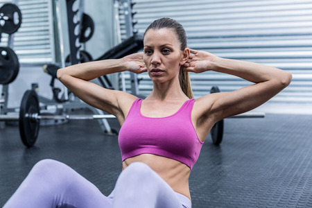Muscular woman doing abdominal crunch at the crossfit gym Stock Photo