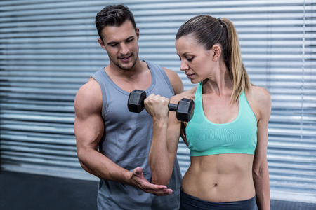 Trainer supervising a muscular woman lifting dumbbells Stock Photo