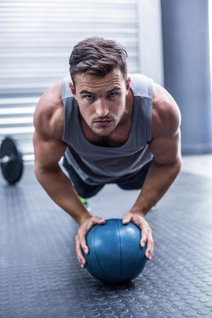 Portrait eines muskulösen Mann auf einem Brett Position mit einem Ball