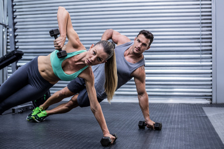 gym room: Portrait of a muscular couple doing side plank while lifting weights Stock Photo