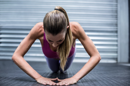 plank position: Muscular woman on a plank position at the crossfit gym Stock Photo