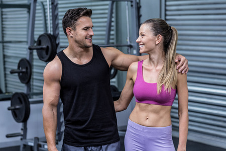 arms around: Muscular couple looking at each other with arms around