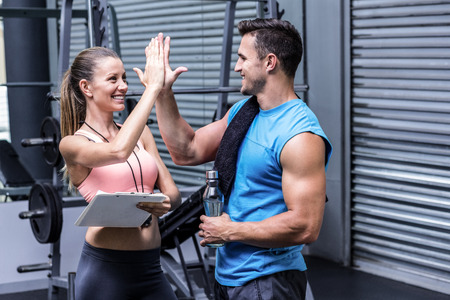 progress: Female coach giving high five with a muscular man
