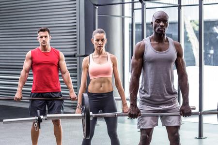 Portrait of three muscular athletes lifting barbells Stock Photo
