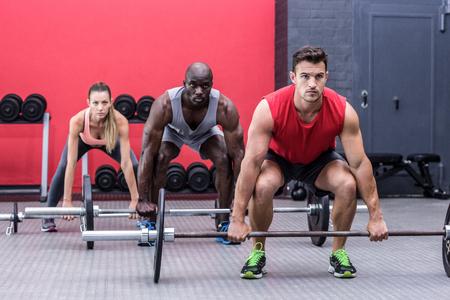 Three muscular athletes lifting barbells at the crossfit gym Stock Photo
