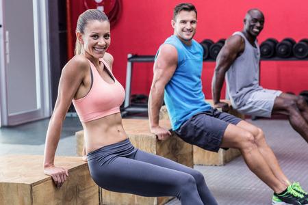 fisico: Retrato de tres atletas muscular que hace empuje hacia arriba inversa