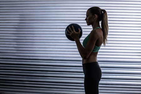 ejercicio: Mujer muscular que hace ejercicio de pelota en un fondo de la sombra Foto de archivo