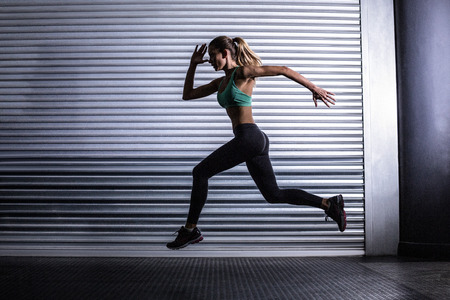 exercise room: Side view of a muscular woman running in exercise room Stock Photo