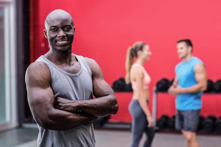 hombres negros: Retrato de un hombre musculoso sonriendo con los brazos cruzados