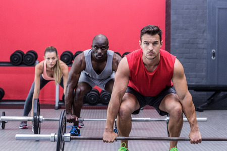 wellness: Portrait of three muscular athletes lifting barbells Stock Photo